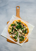 Vegetarian pizza with artichokes, broccolini and shiitake on a wooden board