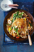 Noodle and vegetable stir fry in a wok