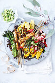 A colourful grill platter with shrimps, fruits, vegetables and black rice
