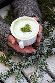 A woman holding a matcha latte