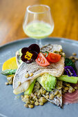 Pan fried sea bass fish fillet on a lentil, broccoli, beetroot, asparagus, tomatoes and edible flowers salad