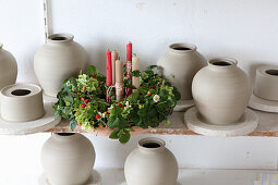 Candles in wreath of strawberry plants surrounded by clay pots