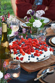 Cake with raspberries on table set for summer party