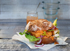A bread roll with cod fingers on paper