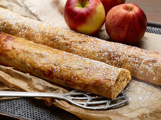 Two whole apple strudels with powdered sugar