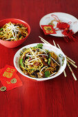 Stir fried egg noodles with sausages, mushrooms, sprouts and sugarsnap peas