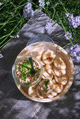 Blinis with trout rillette served outdoors on a wooden table (top view)