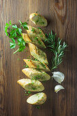 Sliced garlic baguette with herbs on a wooden surface