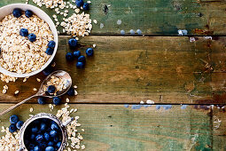 Oatmeal and blueberries in bowls against a rustic wooden background