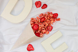 A paper cone with strawberry popcorn (seen from above)