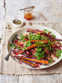 A salad with purple carrots, pomegranate seeds and parsley