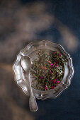 Tea leaves on a metal dish with a spoon