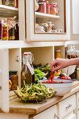 Pickles, fresh fruit and vegetables on a kitchen dresser