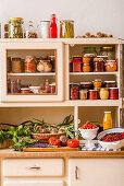 Preserves, fresh fruit and vegetables on a kitchen dresser
