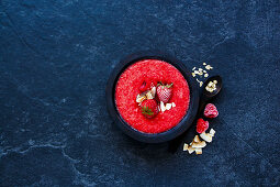 Vintage wooden bowl of tasty berry detox smoothie with frozen berries and oats over dark concrete background
