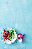 A plate of red chili peppers and fresh herbs on a plate beside several orchid flowers