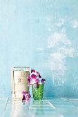 An Asian bamboo steamer beside a glass of orchid flowers