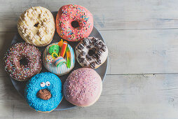 Different variations of the sweet donuts on wooden background with blank space