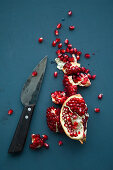 Pomegranate pieces with a knife on a blue background