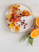 Halved bananas with oranges, grapefruit and pomegranate seeds