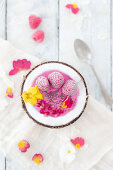 A frozen smoothie bowl with raspberries, pomegranate seeds and edible flowers