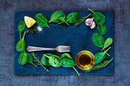 Top view of fresh delicious baby spinach leaves and olive oil on dark slate background