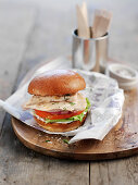 A chicken burger with tomato and salad
