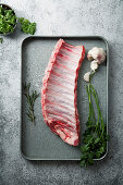 Uncooked pork ribs on metallic tray with herbs and garlic