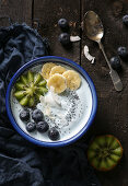 A smoothie bowl with soy yoghurt, fruit, poppy seeds and coconut flakes