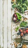 Winter vegetarian, vegan food cooking ingredients, vegetables, fruit, beans, cereals, kitchen utencil, dried flowers, olive oil over white wooden background