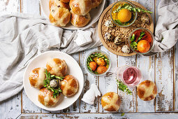 Easter table setting with colored orange eggs, hot cross buns, green branches decorated, empty plate, cutlery, glass of lemonade drink