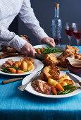 Woman serving Sunday roast dinner