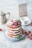 A red velvet cake with vanilla cream and raspberries
