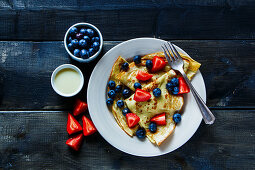 Freshly made thin pancakes or crepes with fresh berries and cream on plate over rustic wooden background