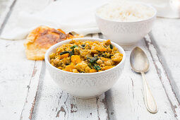 Vegetable curry with cauliflower, butternut squash, spinach and coriander served with poppadoms and rice
