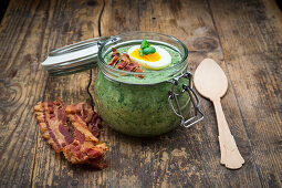 Cream of spinach soup with egg and crispy bacon in a jar