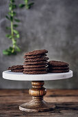 A stack of chocolate biscuits on a cake stand