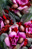 An arrangement of pink shades made from cabbage, plums and flowers (full frame)