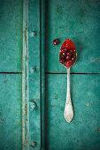 Cornelian cherry jam on a spoon with Cornelian cherries