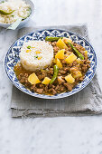 A plate with picadillo con papas garnished with green peppers and served with mexican rice with sweet corn and peas