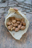 Homemade roasted almonds in a paper bag