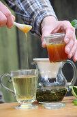 A man adding honey to peppermint tea