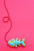 A fish shaped biscuit with blue icing against a pink background
