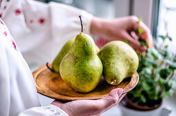 Girl brought pears from the garden to make a pie