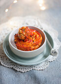 A spaghetti nest with meatballs and stemmed cabbage