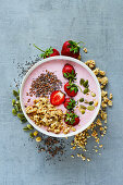 Tasty strawberry smoothie bowl with fruits, cereals, seeds and nuts over light grey background