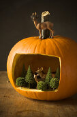 Miniature forest with animals in hollowed-out pumpkin