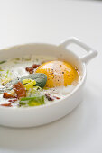 Baked egg with pancetta and onion cream in Ramakin