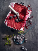 Blackberry sorbet with an ice cream scoop in a metal container