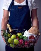 Person hält Drahtkorb mit verschiedenen Lebensmitteln